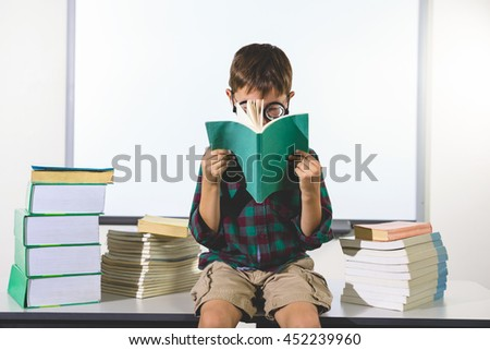 Elementary boy reading book while sitting on table in classroom - stock photo