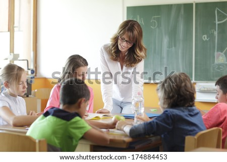 Elementary classroom. Focus on teacher standing in front of chalkboard.