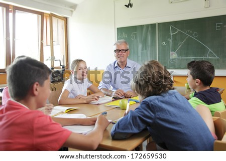 Elementary classroom setting. Focus on teacher and chalkboard. - stock photo