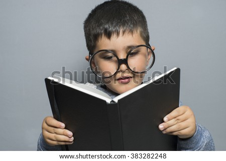 elementary, dark-haired young student reading a funny book, reading and learning