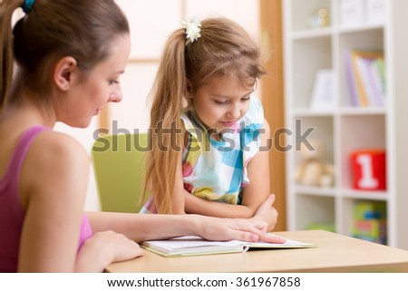 Elementary Pupil Reading With Teacher  - stock photo