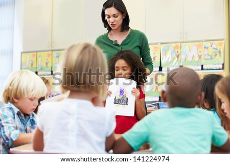 Elementary Pupil Showing Drawing To Classmates In Classroom - stock photo