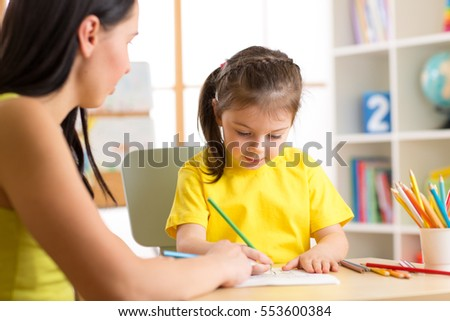 Elementary Pupil Writing and Drawing With Teacher