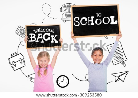 Elementary pupils holding jigsaw pieces against back to school - stock photo