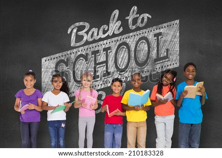 Elementary pupils reading books against black wall with back to school message - stock photo