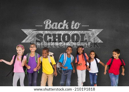 Elementary pupils running against black wall with back to school message - stock photo