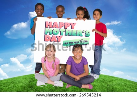 Elementary pupils showing card against green hill under blue sky - stock photo