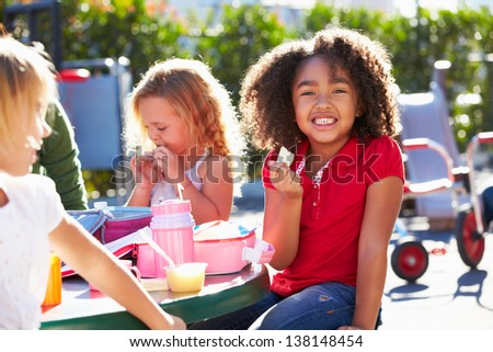 Elementary Pupils Sitting At Table Eating Lunch - stock photo