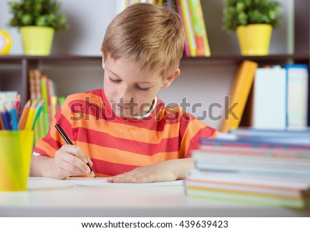 Elementary school boy at classroom desk making homework