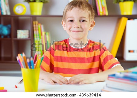 Elementary school boy at classroom desk making  schoolwork - stock photo