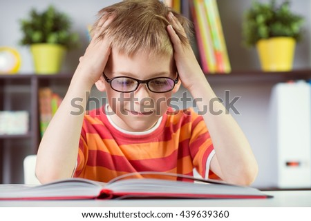 Elementary school boy at classroom desk reading book - stock photo
