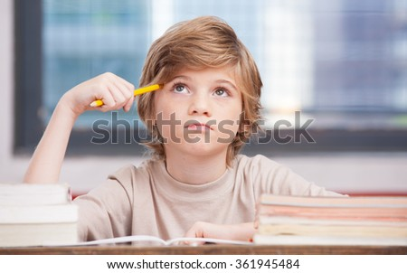 Elementary school boy at classroom desk trying to find new ideas for schoolwork. - stock photo