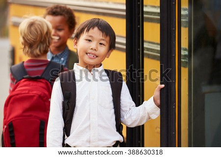 Elementary school boy at the front of the school bus queue - stock photo