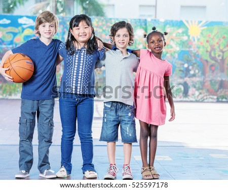 Elementary school children playing basketball at gym.