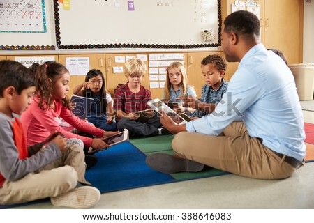 Elementary school class sitting cross legged using tablets