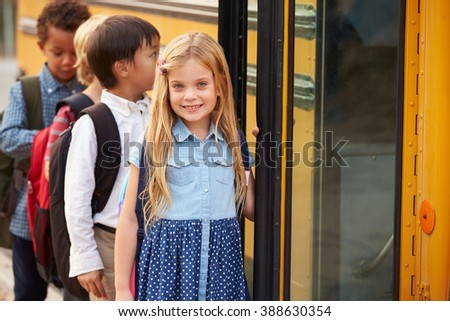 Elementary school girl at the front of the school bus queue - stock photo