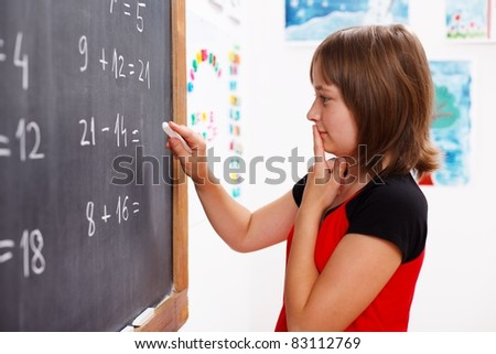 Elementary school girl standing in front of chalkboard and thinking on solution of math equation - stock photo