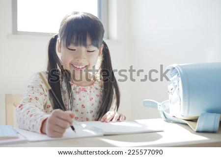 Elementary school girl studying - stock photo