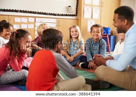 Elementary school kids and teacher sit cross legged on floor - stock photo