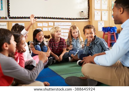 Elementary school kids and teacher sit cross legged on floor - stock photo