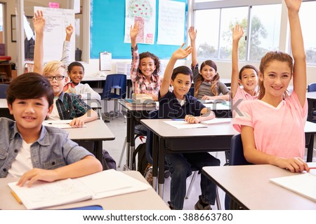 Elementary school kids in a classroom raising their hands - stock photo