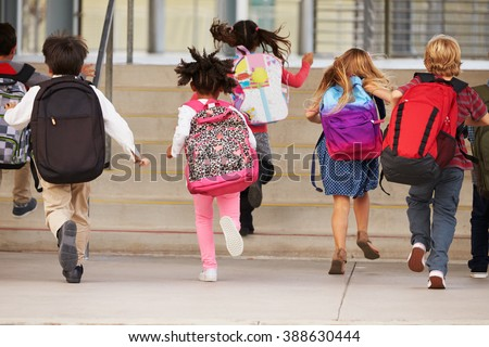 Elementary school kids running into school, back view - stock photo