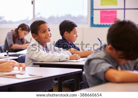 Elementary school kids working at their desks in a classroom - stock photo