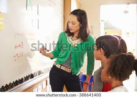 Elementary school maths class at the whiteboard with teacher - stock photo