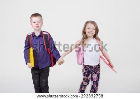 Elementary school pupils boy and girl go to school - stock photo
