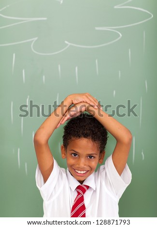 elementary school student in front of rain cloud drawn on chalkboard