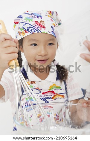 Elementary school student learning to cook