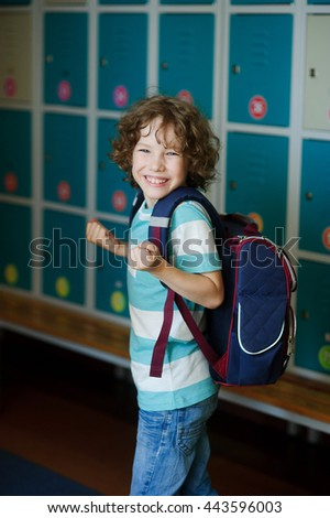 Elementary school student standing near lockers in school hallway. Behind kid's school backpack.