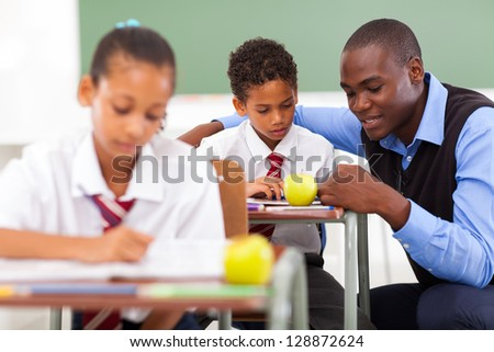 elementary school teacher helping student in classroom - stock photo
