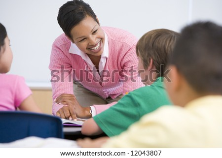 Elementary school teacher with pupils in classroom - stock photo
