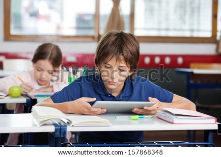 Elementary schoolboy using digital tablet with classmate studying in background at classroom - stock photo
