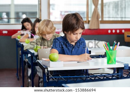 Elementary schoolchildren writing in books at desk in classroom - stock photo