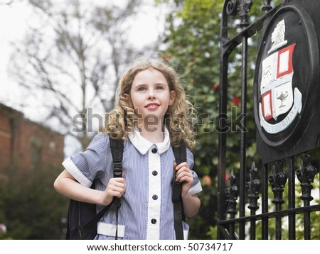 Elementary schoolgirl standing by school gate - stock photo