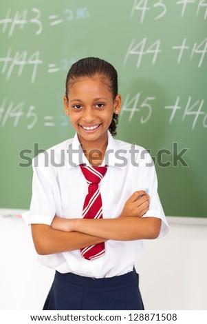 elementary schoolgirl standing in front of  chalkboard - stock photo