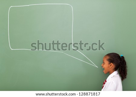 elementary schoolgirl with speech bubble drawn on chalkboard