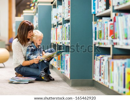 Elementary student with teacher reading book by bookshelf in library - stock photo