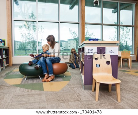 Elementary student with teacher reading book in school library - stock photo