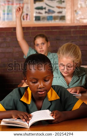 Elementary students working together in the classroom - stock photo