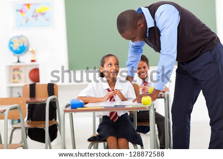 elementary teacher helping student in classroom - stock photo