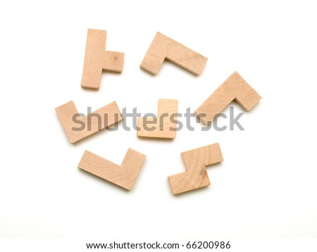 Elements of a wooden puzzle randomly placed on white background - stock photo