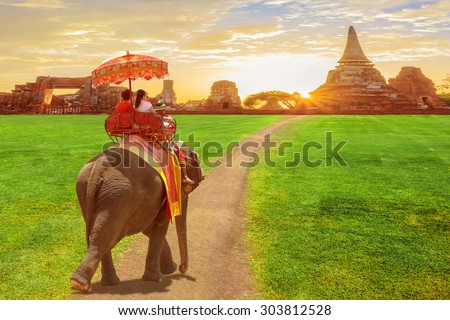 Elephant and tourists on an ride tour of the ancient city in sun rise - stock photo