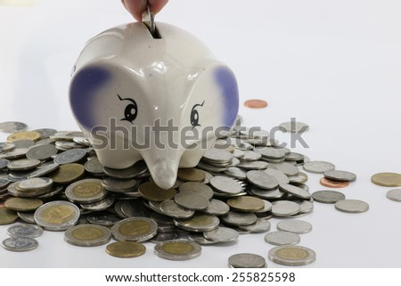 elephant coin bank on a pile of coins.