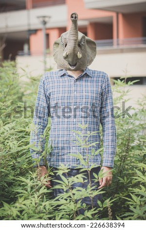 elephant mask absurd man in the plants - stock photo