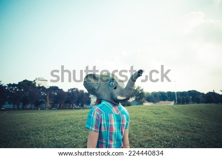 elephant mask beautiful young hipster woman in the city - stock photo