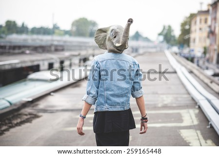 elephant mask young handsome bearded hipster man in the city - stock photo