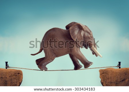 elephant running across a tightrope with motion blur and vintage filter